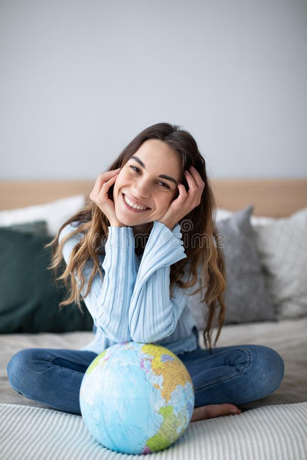 Happy smiling woman with a globe sitting on the bed and looking at the camera stock photography