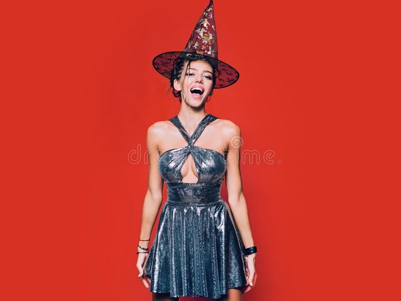 Happy gothic young woman in witch halloween costume with hat standing and smiling over red background. Pretty young stock images
