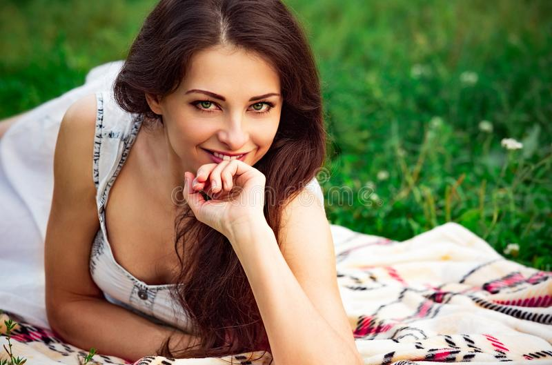 Happy smiling woman with happy look lying on the green summer grass. Closeup royalty free stock images