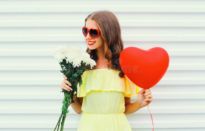 Happy smiling woman holding bouquet flowers and red air balloon heart shape over white. Background stock photography