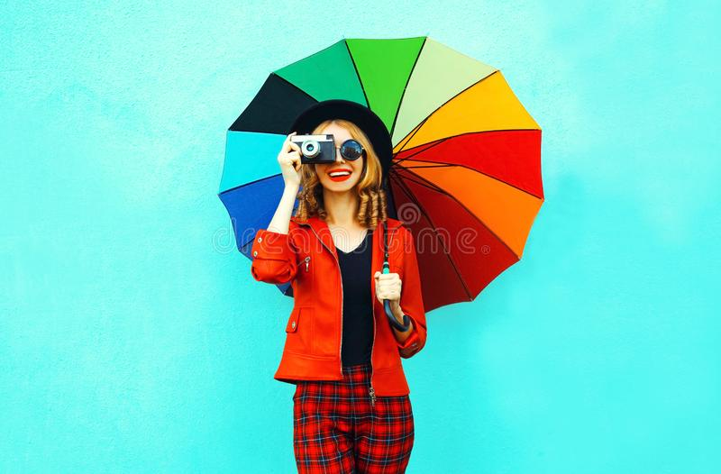 Happy smiling woman holding colorful umbrella, retro camera taking picture in red jacket, black hat on blue wall. Background stock photography
