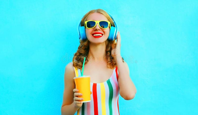 Happy smiling woman holding cup of juice listening to music in wireless headphones on colorful blue. Background stock images