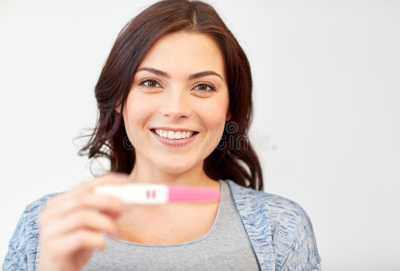Happy smiling woman holding home pregnancy test stock images