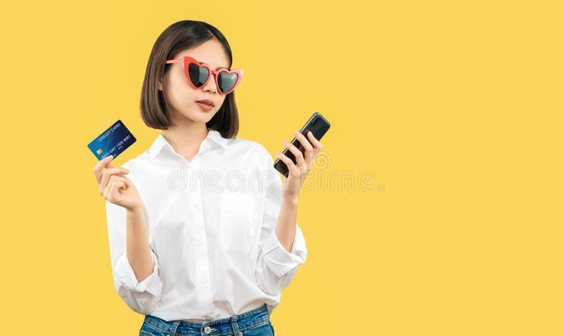 Happy smiling woman holding smart phone and credit card with shopping online. royalty free stock image
