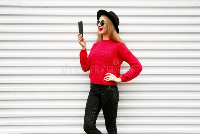Happy smiling woman holding smartphone in colorful pink knitted sweater on city white wall royalty free stock photo