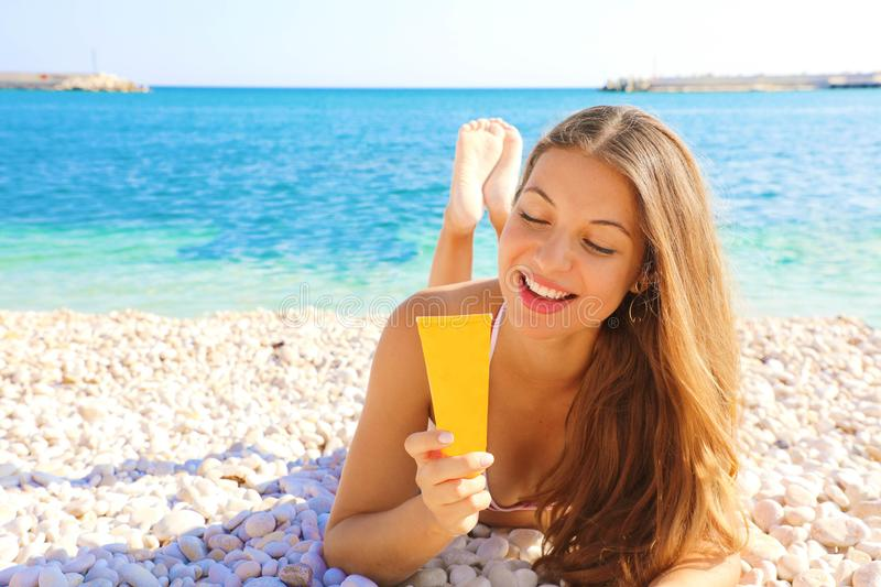 Happy smiling woman holding sun cream tube protection lying on pebbles beach. Sunscreen girl looking suntan lotion in plastic royalty free stock photo