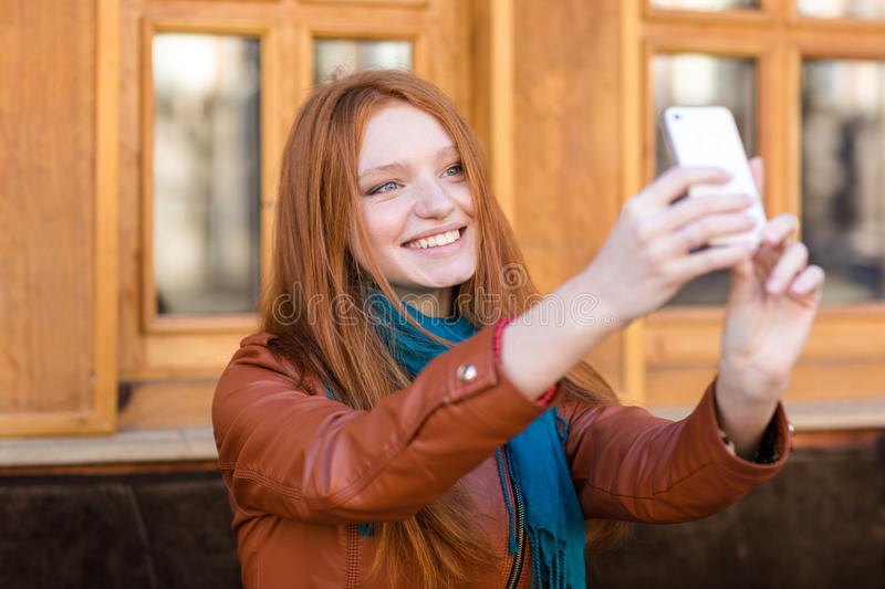Happy smiling woman with long red hair making selfie royalty free stock photos
