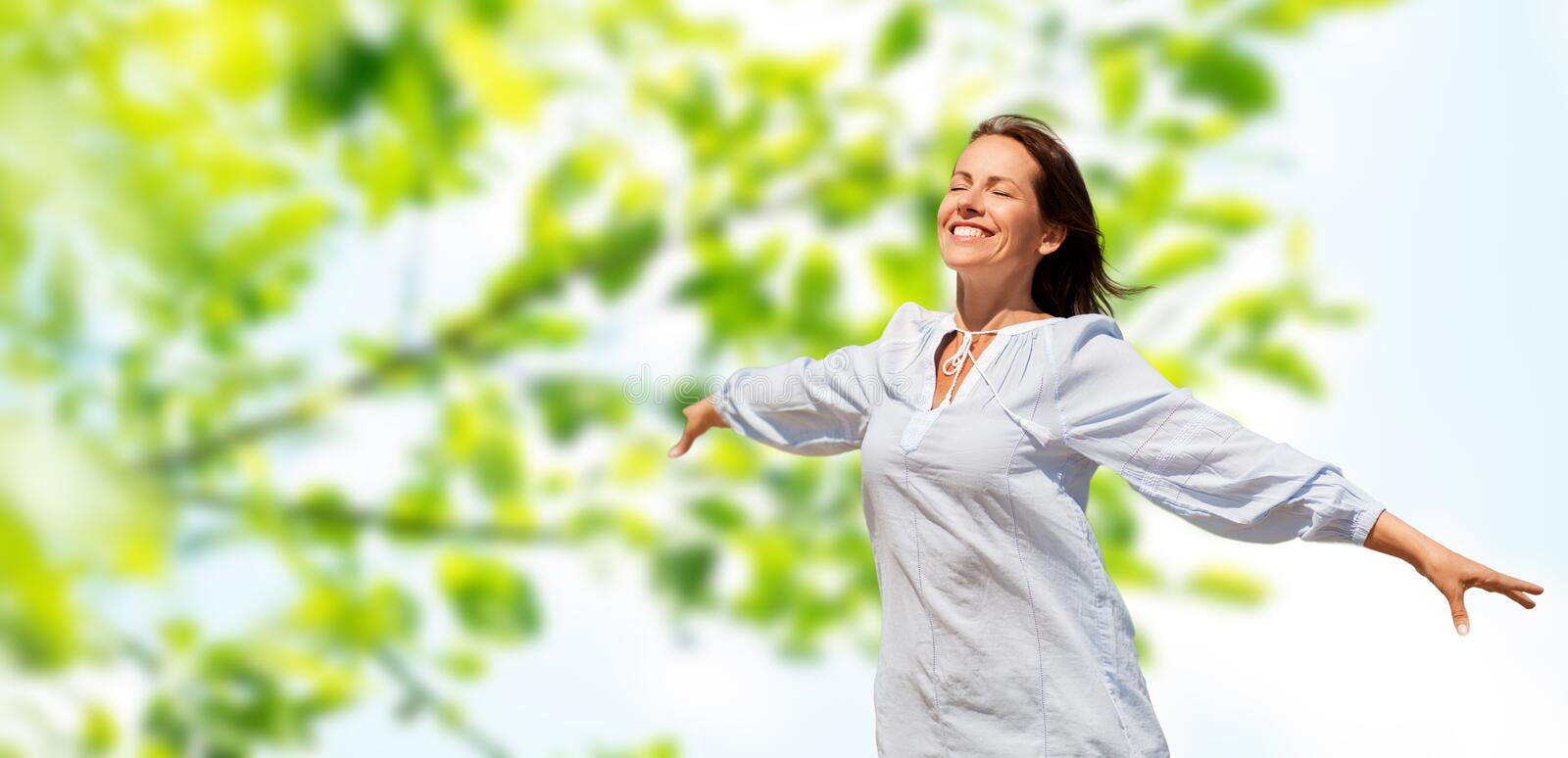 Happy smiling woman over green natural background royalty free stock photo