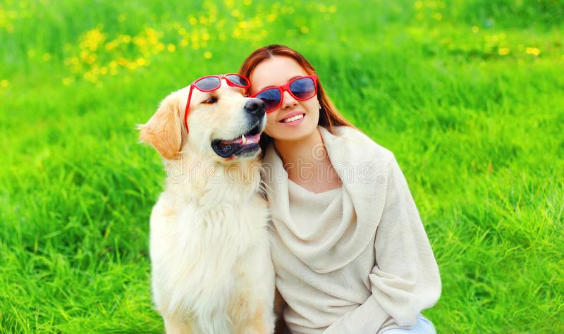 Happy smiling woman owner and Golden Retriever dog in sunglasses together on grass in summer royalty free stock image