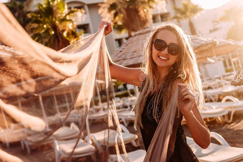 A happy smiling woman is photographed in the contoured sunset light on the beach in summer stock images