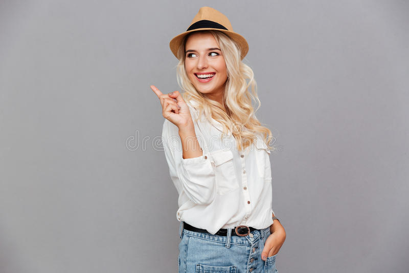 Happy smiling woman pointing finger away royalty free stock images