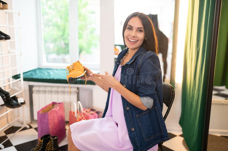 Happy smiling woman pointing at the yellow sneakers in hands stock photos