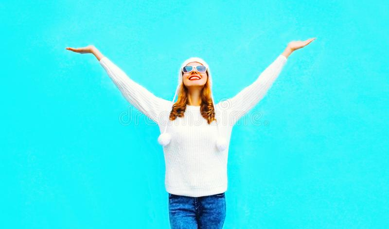 Happy smiling woman raises her hands up wearing white knitted sweater royalty free stock photography