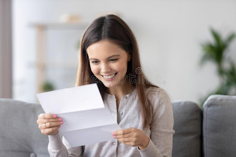 Happy smiling woman reading paper letter, receive good news at home. Happy smiling young woman reading paper letter, receive good news, sitting on sofa at home stock image