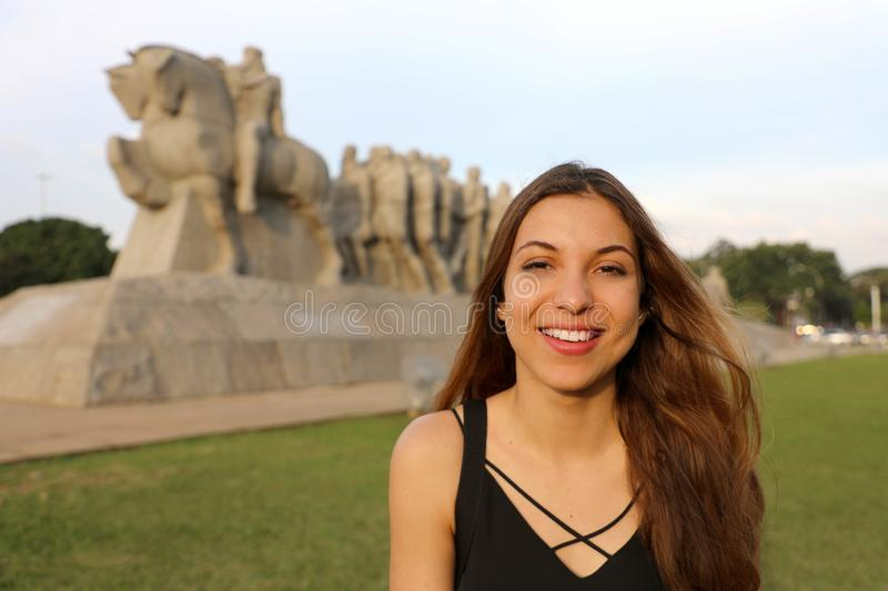 Happy smiling woman in Sao Paulo with Monument to the Bandeiras landmark on the background, Sao Paulo, Brazil royalty free stock image