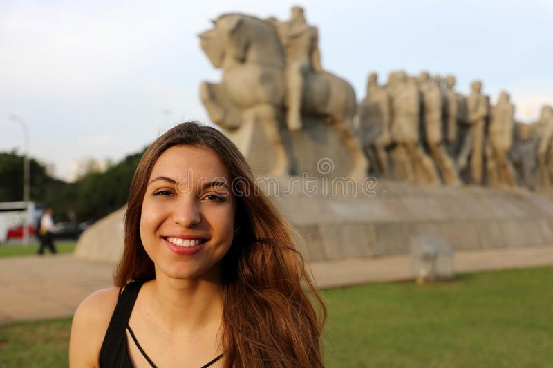 Happy smiling woman in Sao Paulo with Monument to the Bandeiras landmark on the background, Sao Paulo, Brazil royalty free stock photos