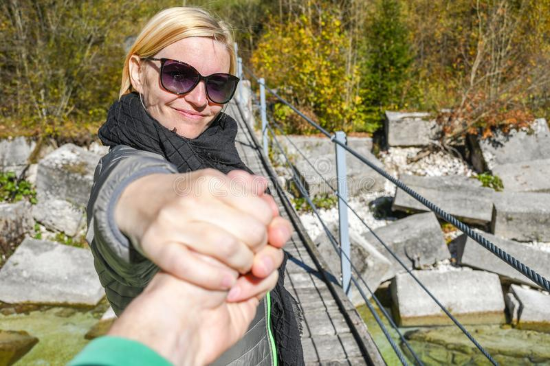 Happy smiling woman standing on a old wooden hanging bridge while holding an arm royalty free stock images