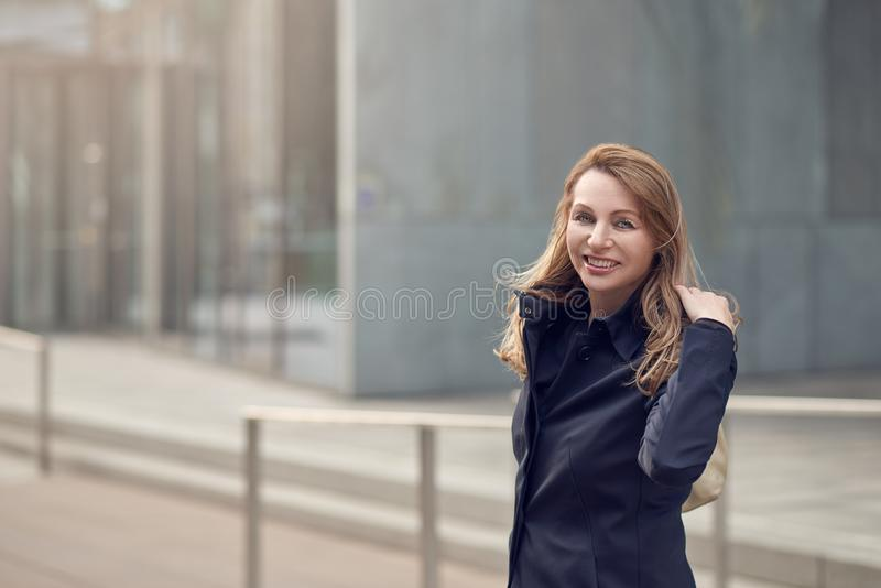 Happy smiling woman standing in the wind on an urban street stock photos
