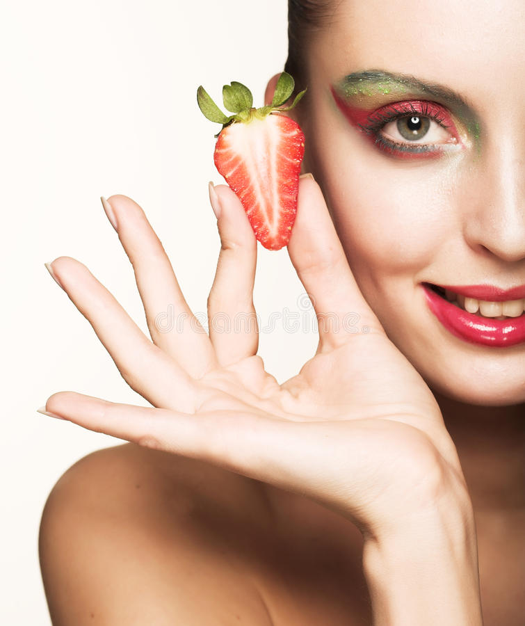 Happy smiling woman with strawberry. Young beautiful happy smiling woman with strawberry royalty free stock photography