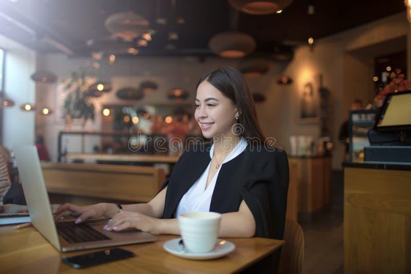 Joyful female website content creator searching information via notebook stock photo
