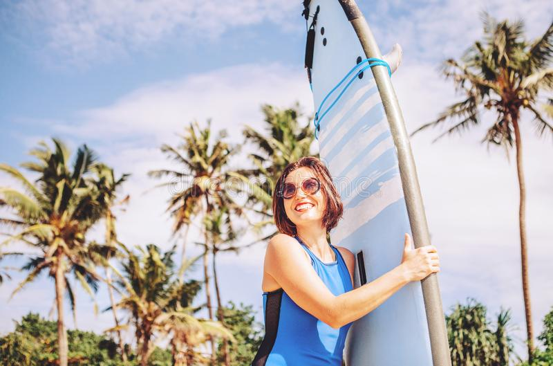 Happy smiling woman with surf board posing on tropical beach royalty free stock photography