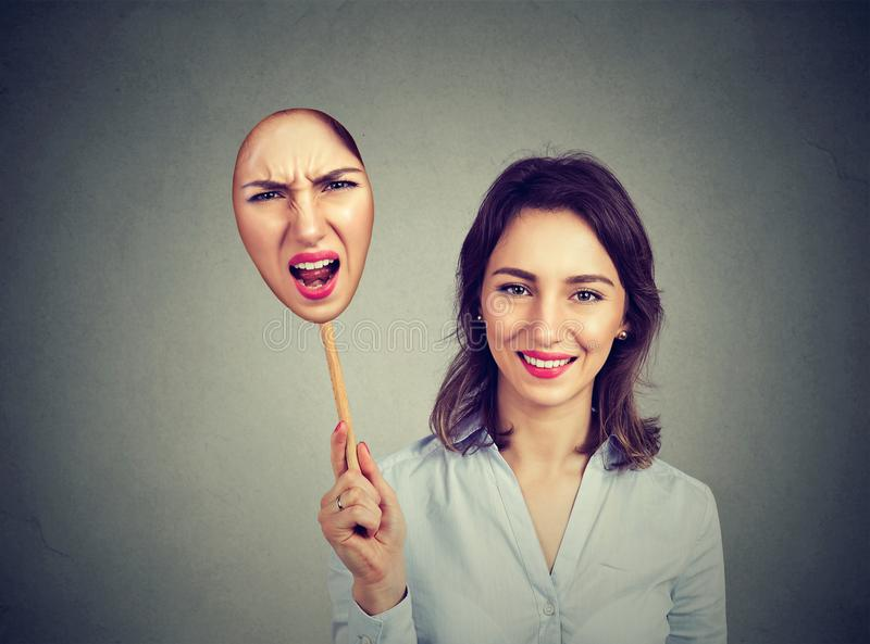 Happy woman taking off an angry mask of herself stock photography