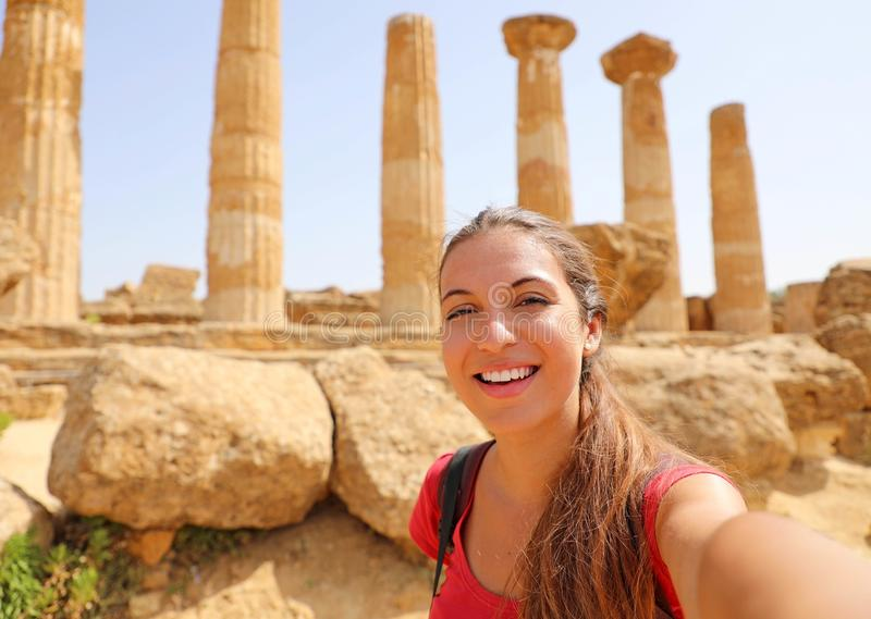 Happy smiling woman taking self portrait with greek temple on the background in the Valley of the Temples at Agrigento, Italy.  stock photography