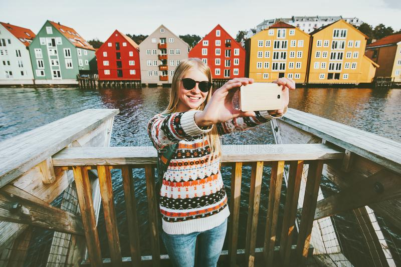 Happy smiling woman taking selfie traveling in Trondheim. City Norway vacations weekend Lifestyle fashion outdoor scandinavian houses landmarks architecture on royalty free stock photos