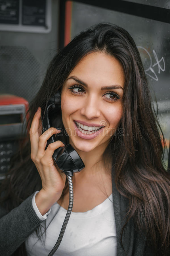 Happy and smiling woman talking in the retro phone booth royalty free stock image