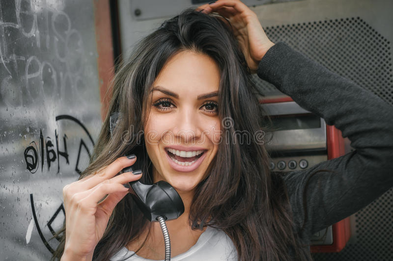 Happy and smiling woman talking in the retro phone booth stock photos