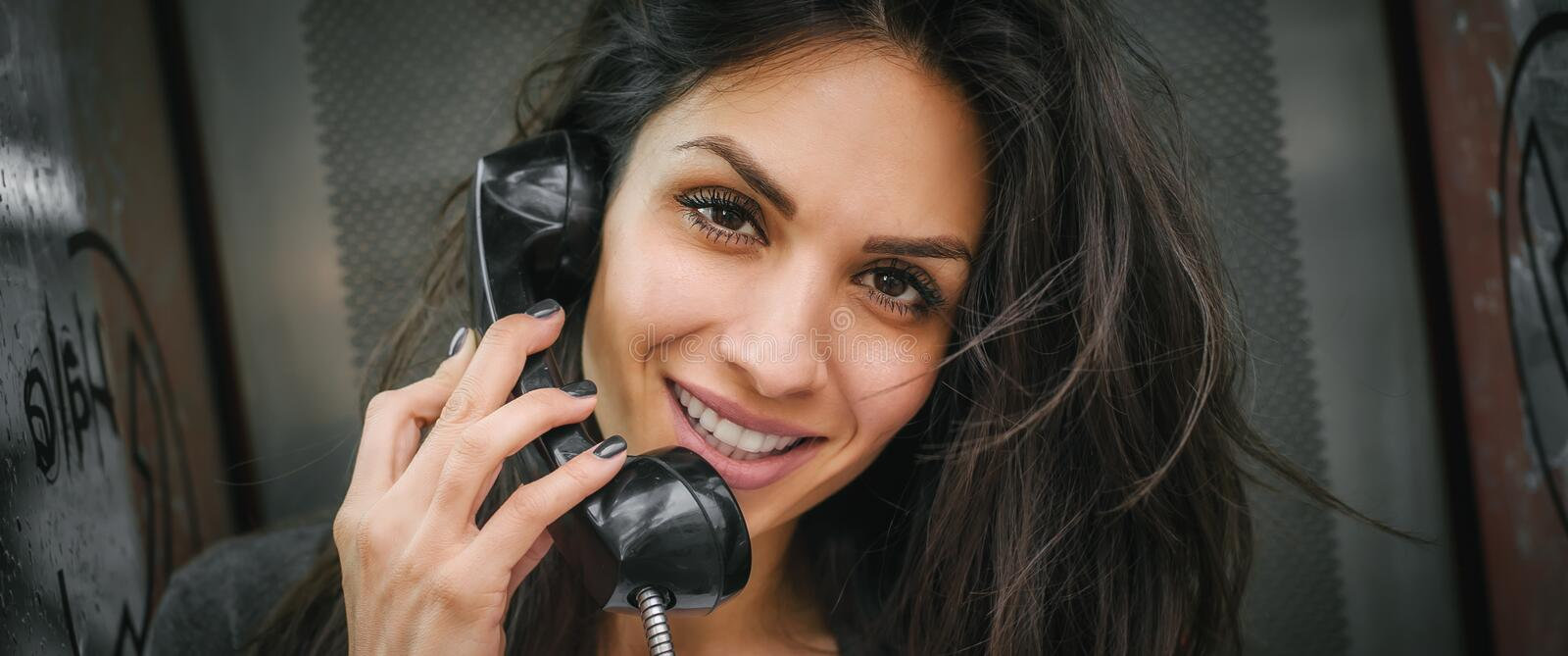 Happy and smiling woman talking in the retro phone booth royalty free stock images