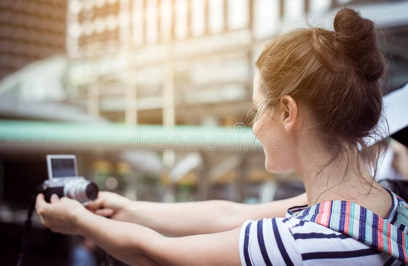 Happy and smiling woman traveler is making her selfie in the city,Beautiful girl walking on the streets. Outdoor stock photo