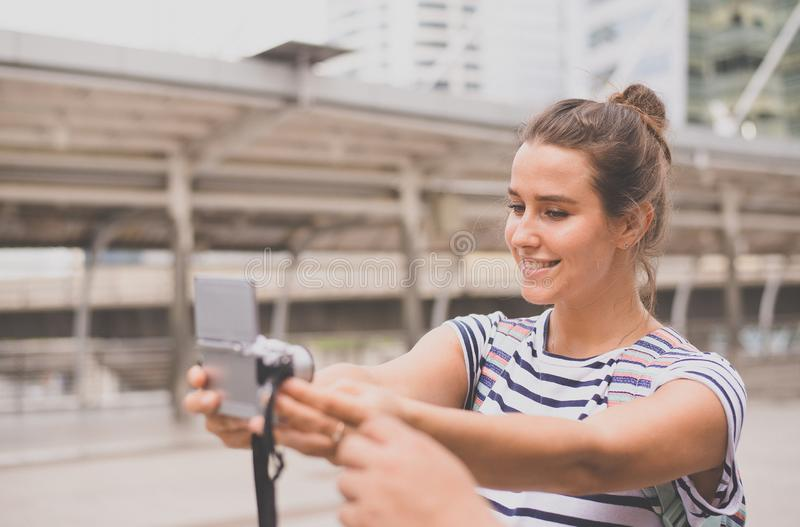 Happy and smiling woman traveller is making her selfie with digital camera in the city,Beautiful girl walking on the streets stock photos