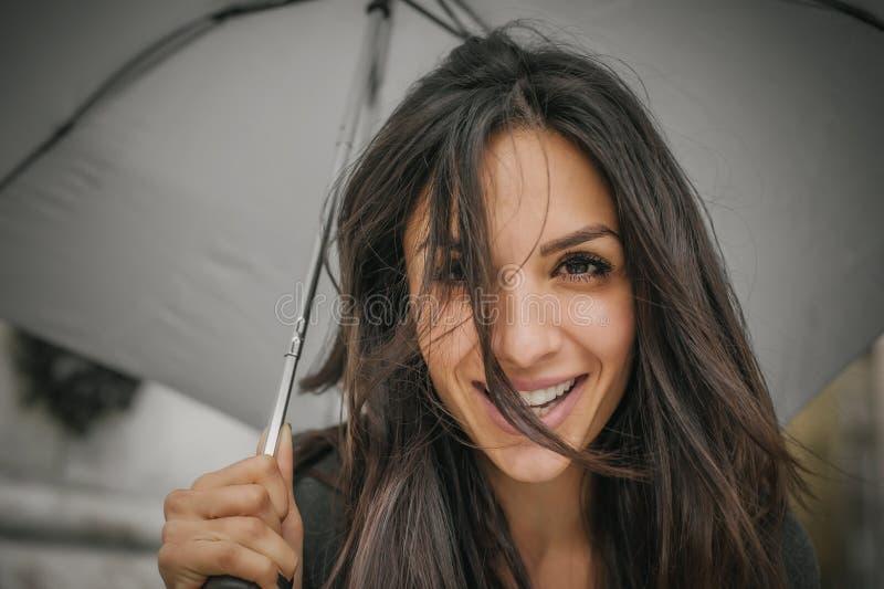Happy smiling woman under umbrella in rain royalty free stock photos