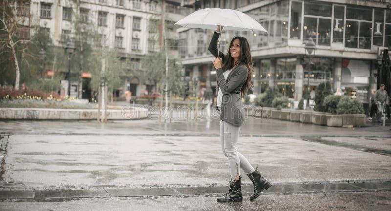 Happy smiling woman under umbrella in rain stock photo