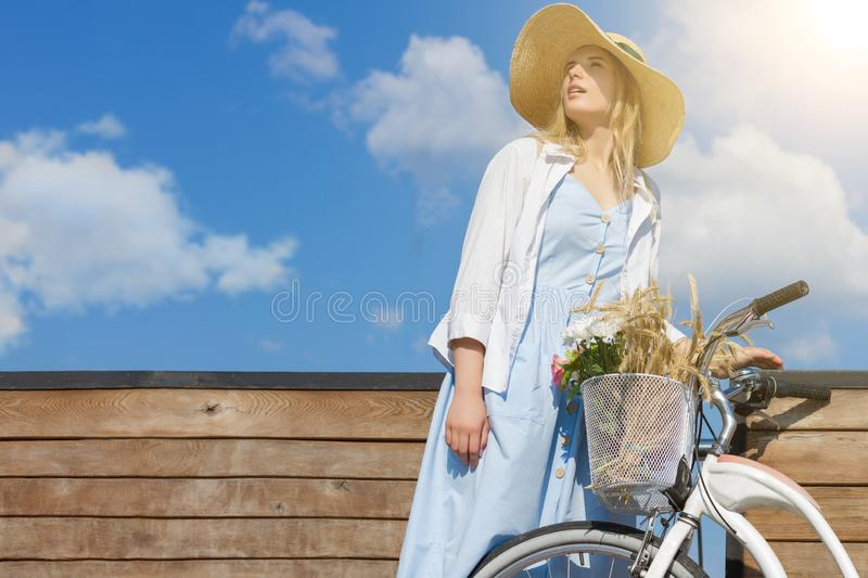 Woman in retro dress straw hat close to bicycle with basket of flowers royalty free stock photo