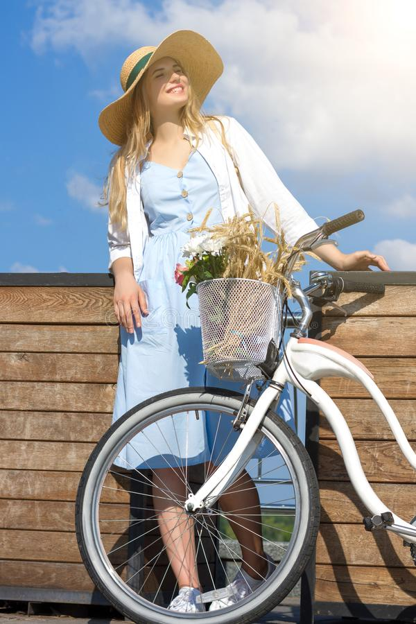Woman in retro dress straw hat close to bicycle with basket of flowers stock photography