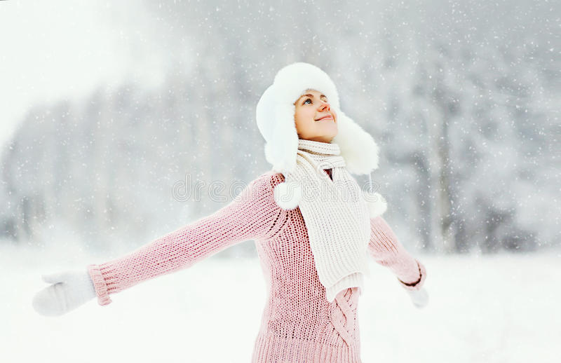 Happy smiling woman wearing a sweater and hat enjoys winter day. Portrait happy smiling woman wearing a sweater and hat enjoys winter day royalty free stock image