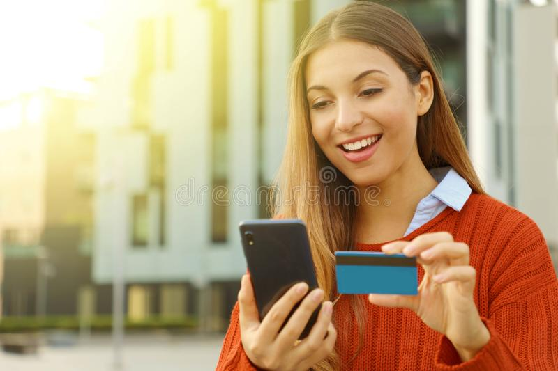 Happy smiling woman wearing sweater paying online holding with smart phone and credit card outdoors in autumn season. Copy space royalty free stock photography