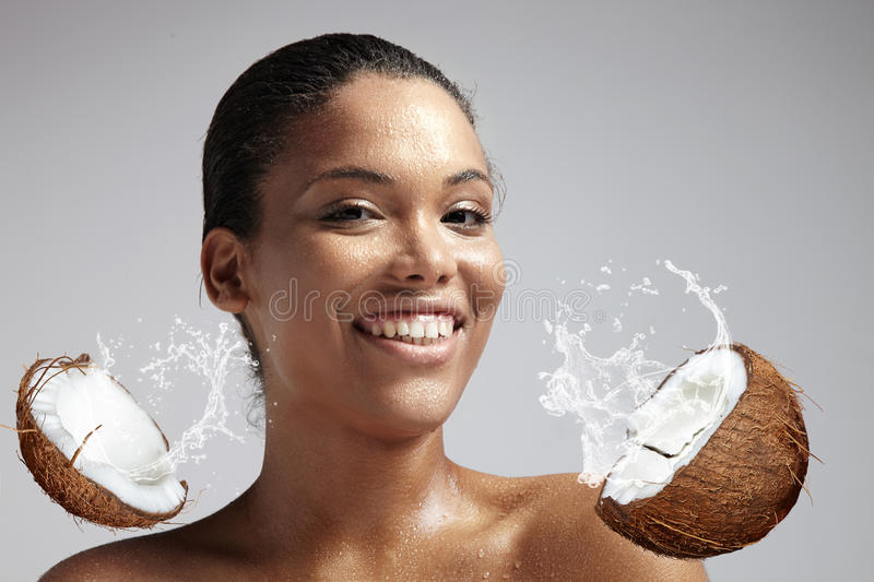 Happy smiling woman with a wet skin from cocnut's milk royalty free stock images