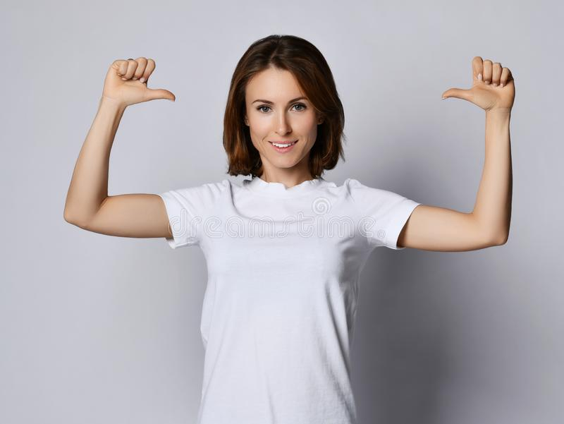 Happy smiling woman in white t-shirt pointing at herself with  her thumbs stock photography
