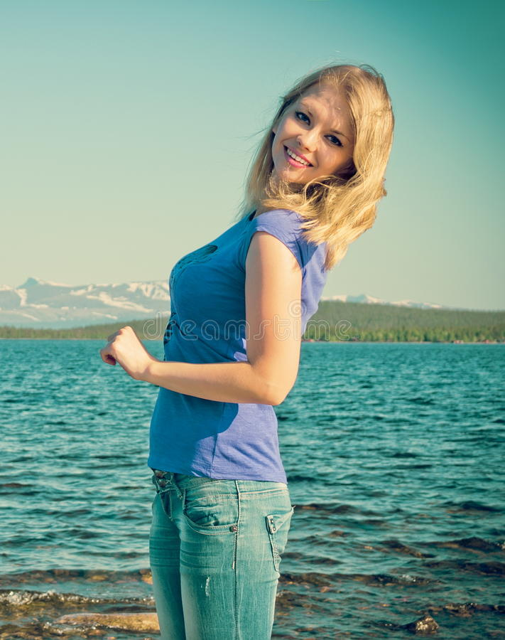 Happy Smiling Woman young Outdoor Lifestyle Traveling. Concept with lake and mountains on background trendy retro colors royalty free stock images