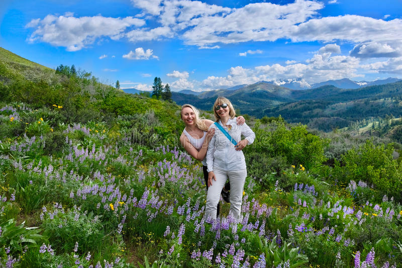 Happy smiling women hiking in meadows among wildflowers. royalty free stock photography