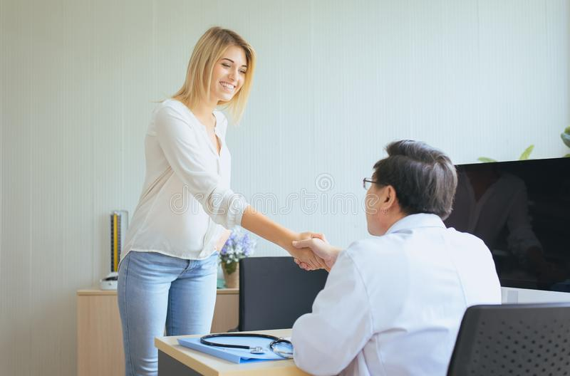 Happy and smiling woman patient giving handshake to man doctor at the hospital,Thank you stock photo