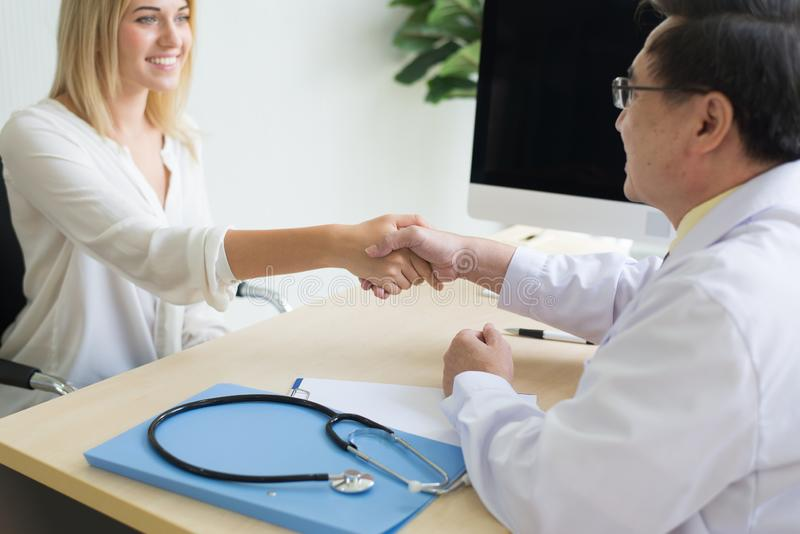 Happy and smiling woman patient giving handshake to man doctor at the hospital stock photos