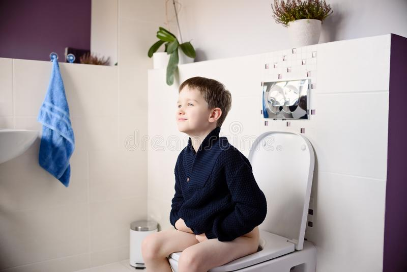 Boy sitting on the toilet stock image. Image of cheerful