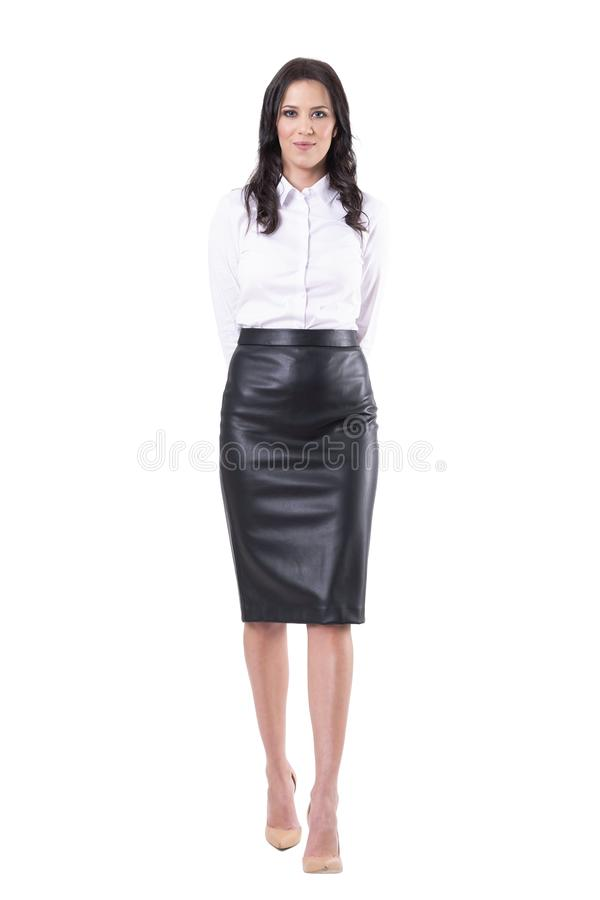 Happy smiling young adult business woman or teacher walking towards camera with hands behind back stock photo