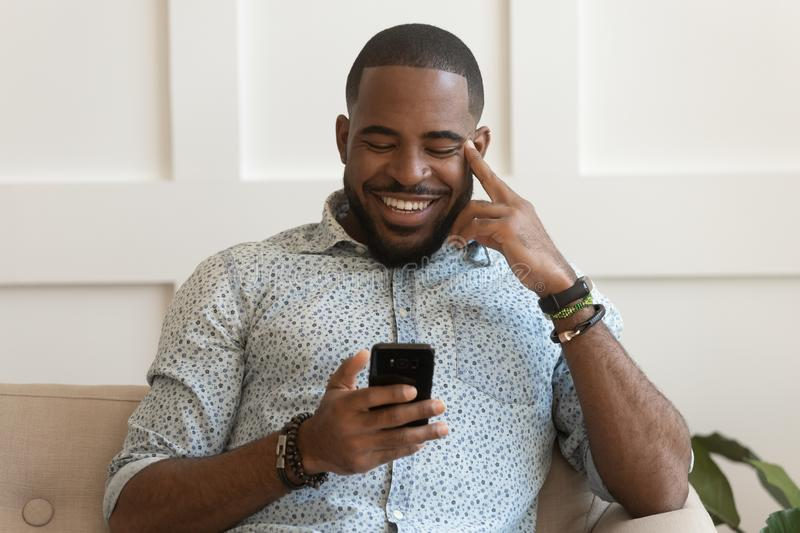 Happy smiling young african american guy holding cell phone. royalty free stock image