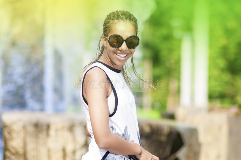 Happy Smiling Young African American Teenager Girl With Plenty of Dreadlocks Posing in Park Outdoors. stock photography