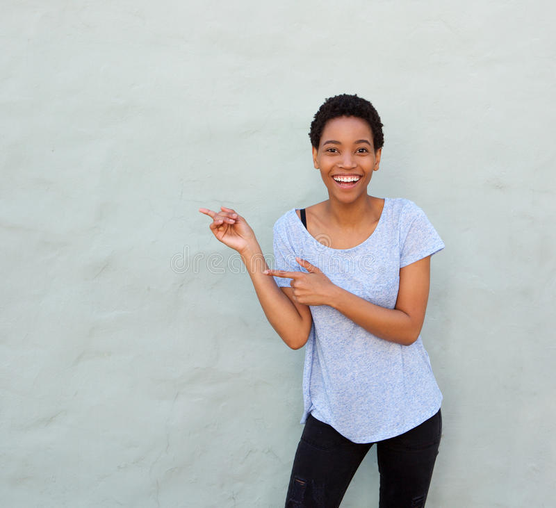 Happy smiling young african woman pointing fingers stock image